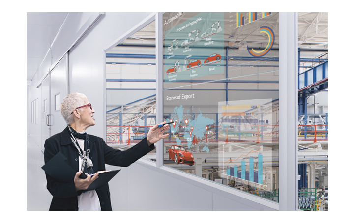 A woman understands her work by looking at the transparent display installed in the office's windows.