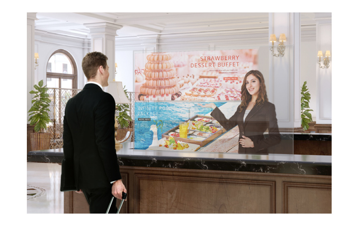 A man is getting information through the Transparent OLED screen showing photos of the dessert menu.