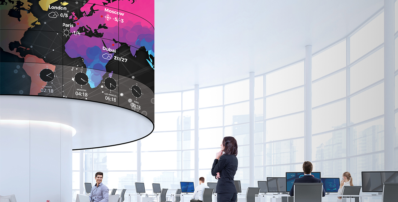 The woman is looking at the weather and time information displayed on the curved screen.
