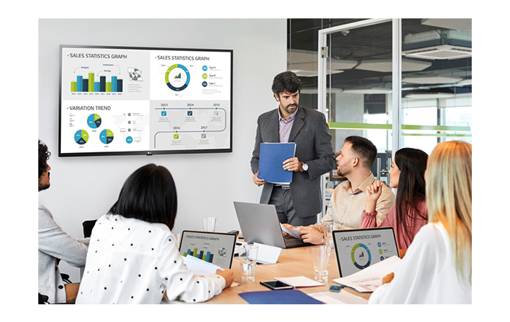 There are 6 people having a meeting and 4 PC screens are simultaneously shared on large signage hanging on the wall through the USB dongle device connected to the personal PCs.