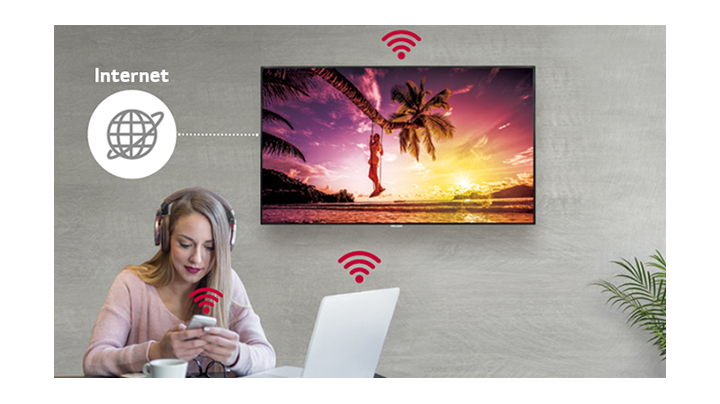 The UM3DG-H series is on the wall and a woman using a personal PC and mobile phone. And this image shows that the signage can be connected wirelessly to the PC and mobile phone she is holding.
