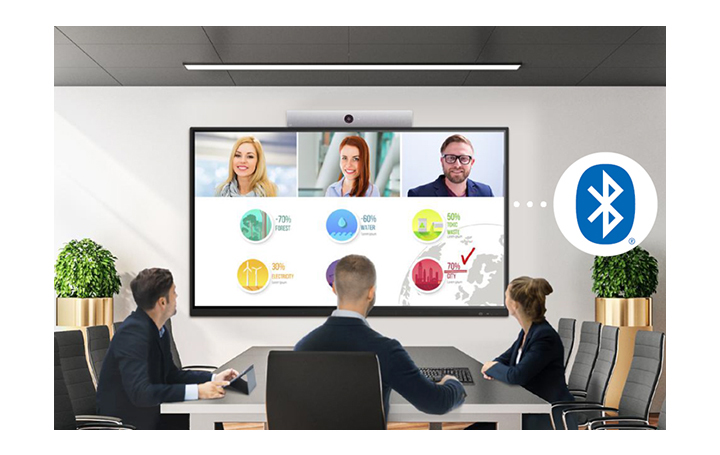 Three people are gathered in a conference room, having a virtual meeting with other people who are appearing on the screen.