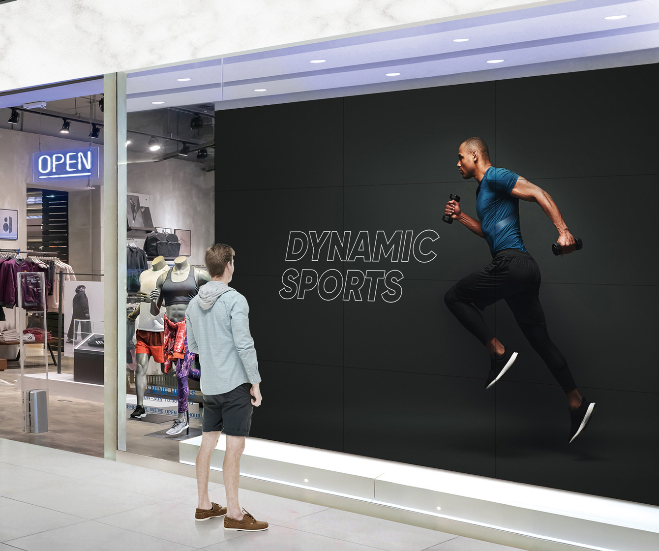 A man is looking at a big screen attached to the window of a sports store.