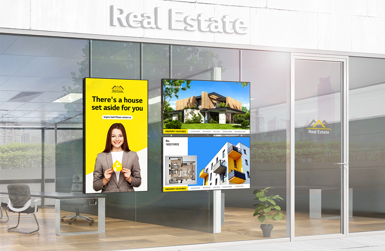 """Inside the full glass of a real estate agency's office, """"High Brightness Window Facing Displays"""" are installed vertically and horizontally facing outward, and thanks to the high brightness of the displays, the ads on the internal display are very visible even from outside with strong sunlight."""